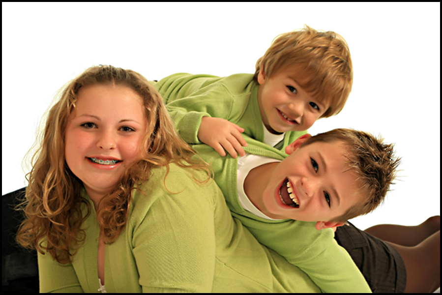 High-Key studio portrait of 3 children in green jumpers with smiles