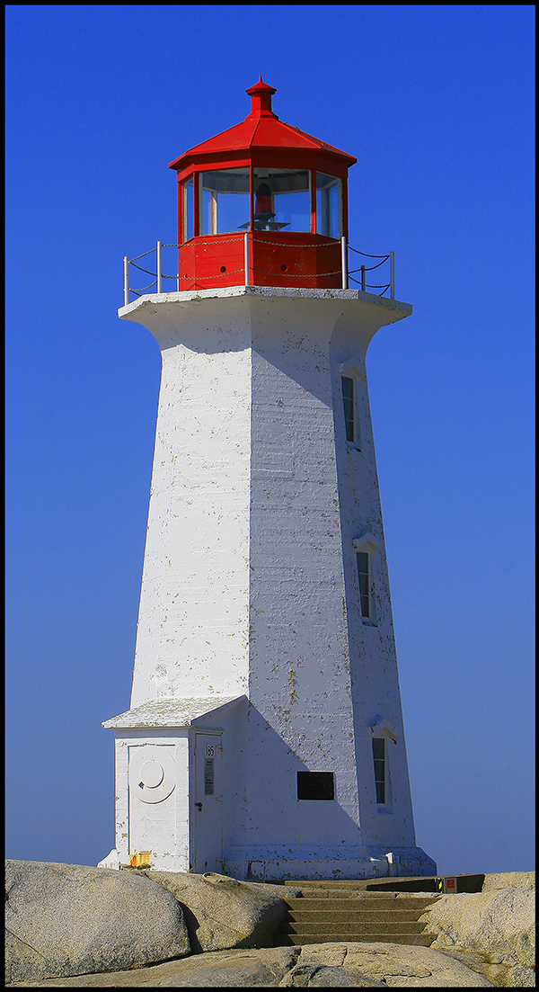 White lighthouse with a red roof against a clear blue sky at Peggys Cover Lighthouse, Nova Scotia, Canada